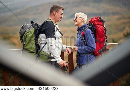 An elderly couple in love chatting and enjoying the view on the top of a watchtower in the forest on a beautiful autumn day