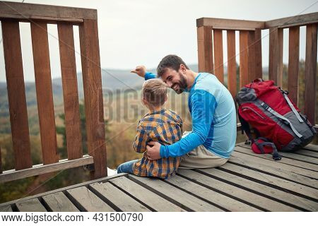 Father and son sitting on the top of a watchtower in the woods on a beautiful autumn day