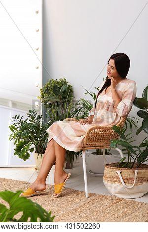 Beautiful Woman Sitting In Wicker Armchair Near Houseplants Indoors. Interior Design