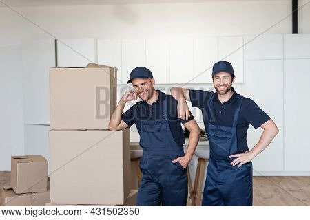 Joyful Movers Smiling At Camera Near Cardboard Packages In Kitchen