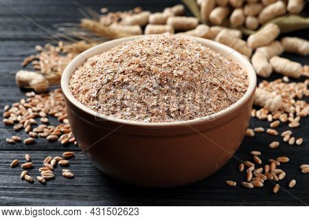 Bowl Of Wheat Bran On Black Wooden Table