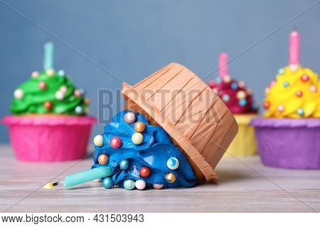 Dropped Cupcake Among Good Ones On White Wooden Table, Closeup. Troubles Happen