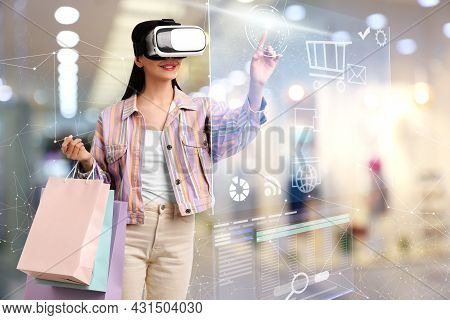 Young Woman With Shopping Bags Using Virtual Reality Headset In Simulated Store