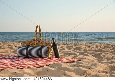Blanket With Picnic Basket And Bottle Of Wine On Sandy Beach Near Sea, Space For Text