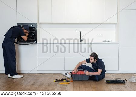 Repairman Fixing Electric Oven Near Colleague Sitting On Kitchen Floor With Toolbox