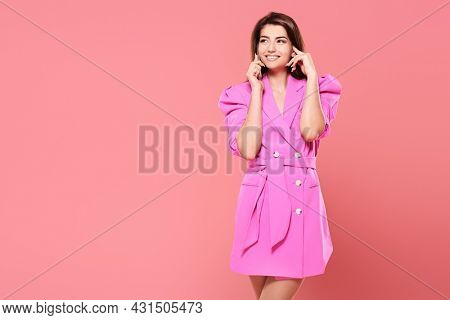 Beautiful happy girl in bright fuchsia dress talks on the phone and smiles. Studio portrait on a pink background with copy space.
