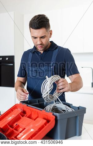 Workman Holding Wires Near Toolbox In Kitchen