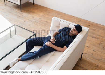 High Angle View Of Tired Mover Relaxing On White Sofa Near Glass Table