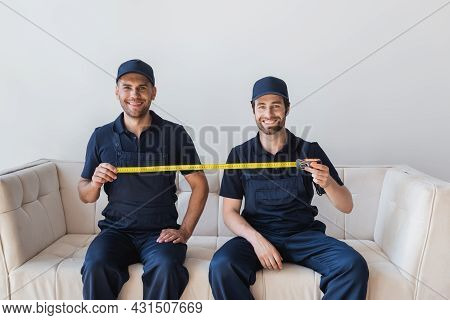 Cheerful Movers Sitting On Sofa And Holding Measuring Tape