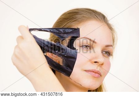 Young Woman Removing Carbo Black Peel-off Mask From Her Face, On White. Teen Girl Taking Care Of Oil