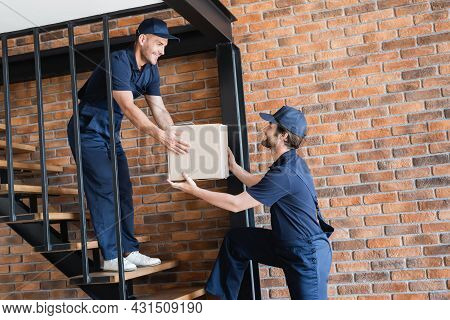 Mover Giving Cardboard Package To Positive Colleague Standing On Stairs
