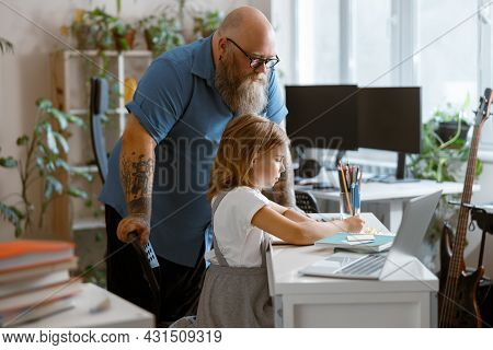 Bearded Plump Father Stands Looking At Little Girl Doing Hometask At Home