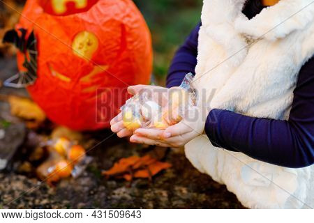 Closeup Of Toddler Girl Trick Or Treating On Halloween. Happy Child Outdoors Counting Sweets From Pu