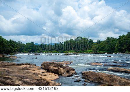 River Flows Between Rocks In Rainforest Under Blue Cloudy Sky Chalakudy Kerala