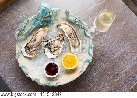 Fresh Open Oysters With Sauce, Lemon And A Glass Of Wine