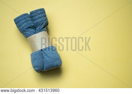 Rolled Folded Men Boxer Briefs With Brown Paper On A Yellow Background