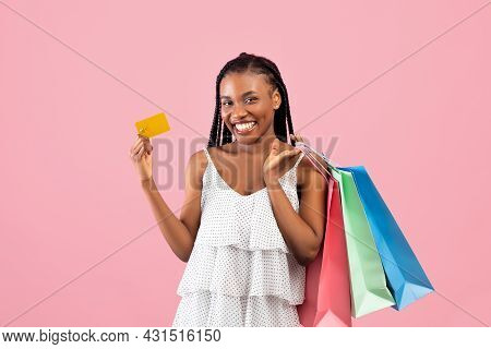 Time For Shopping. Cheery Young Black Female Customer Holding Shopper Bags And Credit Card On Pink B