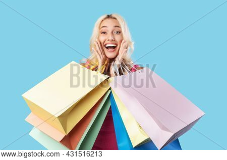 Excited Blonde Woman Holding Shopping Bags At Studio