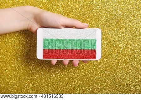 A Woman's Hand Holds A Phone With A Splash Screen Of The Bulgarian Flag On A Golden Background.backg