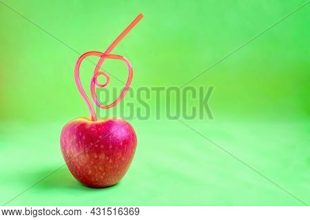 Close-up Of Red Apple In Shape Of Heart With Tube Sticking Out Of It On Bright Green Background With