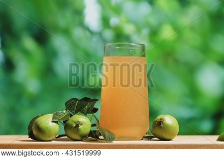 Pear Juice On Wooden Table Outdoors. Glass Of Fresh Juice And Branch Of Pears Fruits, Summer Garden