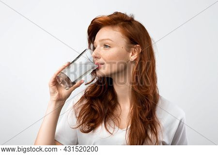 Red-haired Millennial Woman Drinking Water From Glass, Gray Background