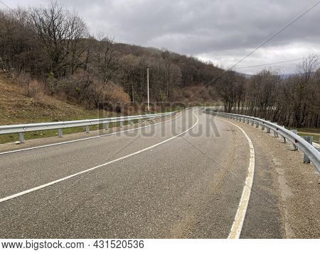 Winding Roadway In Mountainous Terrain. Unrecognizable People Walking Along Road In Distance