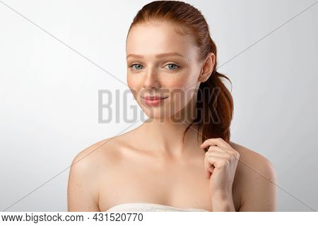 Red-haired Female Touching Her Red Hair In Ponytail, Gray Background