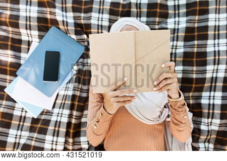 Millennial Arabian Islamic Female In Hijab Lies On Plaid With Phone With Blank Screen And Reads Book