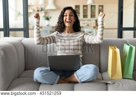 Emotional Young Lady With Laptop And Shopping Bags Buying Things Online On Sale, Purchasing Goods On
