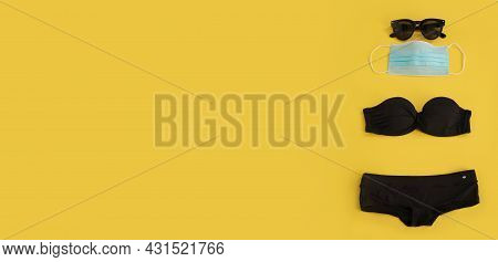 Sunglasses, Medical Mask And Black Bikini On The Yellow Background. Free Space For Text, Copy Space.