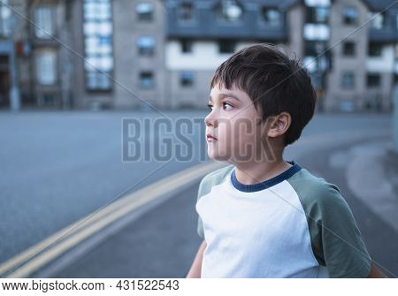 Cute Young Boy Looking Out With Curious Face, Side View Portrait Mixed Race Kid Standing Alone On St