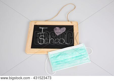 I Love School Text On Slate Blackboard With Pandemic Virus Covid Mask On Grey Background