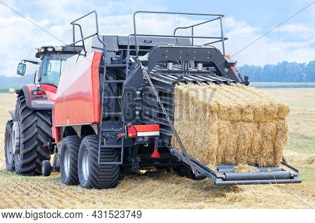 During Harvesting, A Tractor Forms Sheaves Of Straw Into Dense Briquettes In A Wheat Field. Close-up