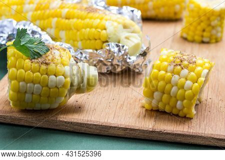 Boiled Corn  And Boiled Corn In Foil On Wooden Board. Green Background. Close Up