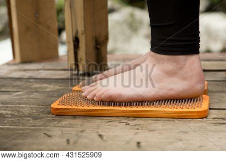 Practice Of Standing On Nails. Close-up Of A Yoga Man Standing On A Sadhu Board With Sharp Nails. Wo
