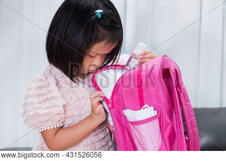 Back To School Concept. Cute Girl Is Preparing Bags For School. Child Puts A Bottle Of Alcohol Gel I