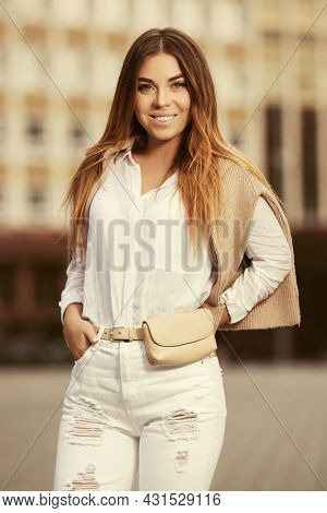 Happy young fashion woman walking on city street Stylish female model with pullover in white shirt and ripped jeans
