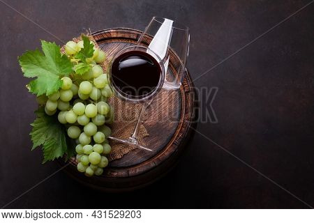 White grape and red wine glasses on old wooden wine barrel. Top view flat lay with copy space