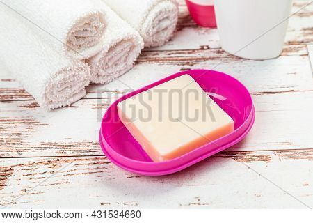 Soap On Pink Plastic Soap Dish With Towels On White Wooden Table In Bathroom