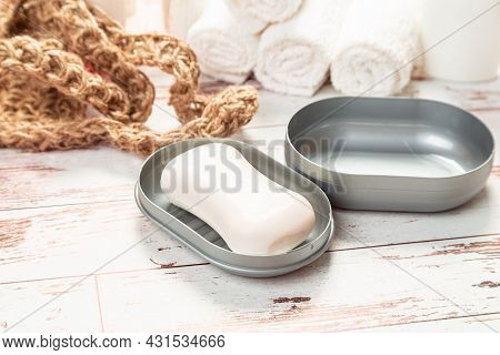 Soap On A Gray Plastic Soap Dish, On A White Wooden Table.