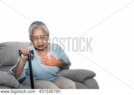 Asian Elderly Woman, Sitting On A Sofa And Holding Walkers In Home, Are Suffering From Angina Due To