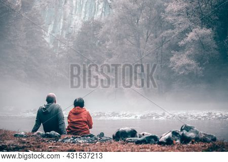 Romanic couple contemplating the beautiful landscape of foggy river.