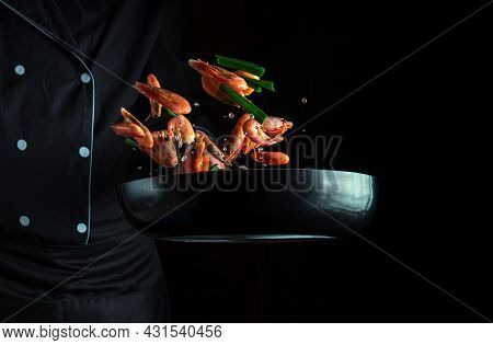 Cook Or Chef Cooks Shrimp In A Pan With Vegetables. Cooking Seafood, Healthy Vegetarian Food And Foo