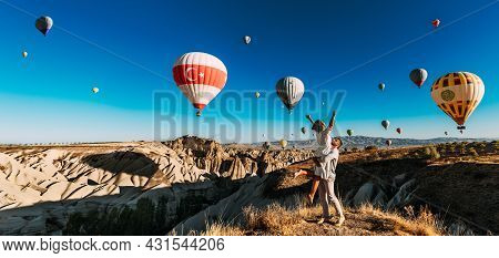 A Happy Couple Among Balloons In Cappadocia. A Couple In Love Against The Background Of Flying Ballo