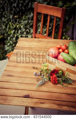 Homegrown Vegetables In A Basket, On A Wooden Table - A Rural Scene