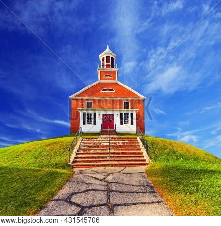 Church at top of a green hill with a grass and an asphalt path hail on the hill