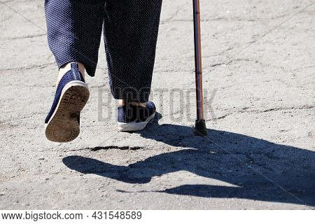 Woman Walking With A Cane On A Street, Female Legs On Sidewalk. Concept Of Disability, Limping Perso