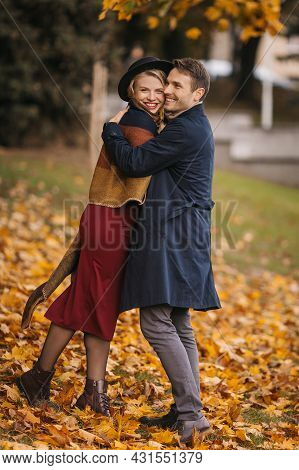 Happy Heterosexual Couple Hugs While Walking At The City Park On The Autumn Day. Handsome Man Hugs H