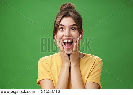 Portrait Of Happy Delighted And Surprised Young Feminine Girl In Yellow T-shirt Pressing Hands To Ch